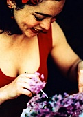 Woman in red summer dress eating; lilac