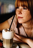 Freckled young woman with latte macchiato