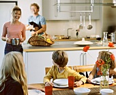 Children at dining table in kitchen, mother bringing a pot