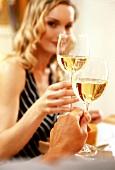 Blond woman chinking white wine glass