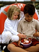Two children eating ice cream from one bowl