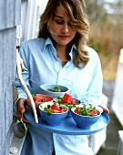 Woman carrying tray of melon salad with sesame and cress