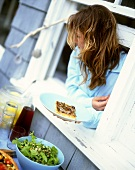Woman at window holding plate with piece of anchovy pizza