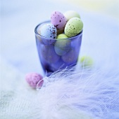 Coloured quail's eggs in a glass