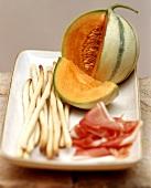 Antipasti still life with ham, honeydew melon and grissini
