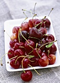 Various types of cherries on white platter