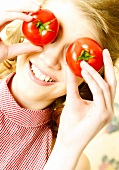 Girl with holding tomatoes in front of her eyes