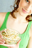 Young sporty woman holding fresh sprouts