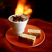 Beaker of hot chocolate & two pieces of nut cake by fireside