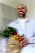 Man carrying bag of vegetables into kitchen