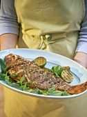 Woman holding platter of red snapper with tamarind puree