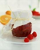 Jar of raspberry and orange jam, three raspberries beside it