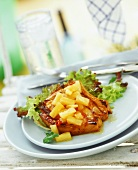 Pork chop with pieces of fresh pineapple and salad leaves