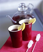 Two beakers of fruit tea with lemon wedges, sugar sticks