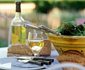 Table laid in open air with salad, bread and wine