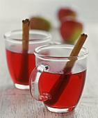 Two glass mugs of mulled wine with cinnamon sticks