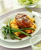 Beef steak on mashed potato and pumpkin with green asparagus