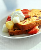 Two slices of Madeira cake with dried fruit, fresh fruit