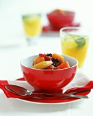 Fruit salad in a red bowl, a spoon beside it