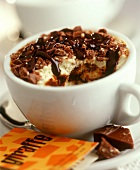 Layered sponge dessert with chocolate in a cup