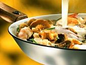 Pouring Béchamel sauce into casserole with mushrooms & shrimps