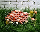 Chipolata sausages on a grill rack in grass