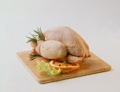 Trussed boiling fowl on wooden board