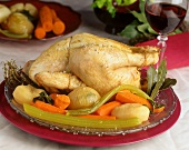 Whole cooked chicken with sea salt on bed of vegetables