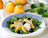 Spinach salad with orange wedges and langouste surimi