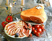 Whole air-dried ham, sliced on plate