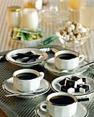 Three coffee cups and sugar lumps