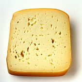 A slice of Tilsit cheese with rind