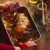 Succulent roast lamb with pistou on bed of potato and tomato