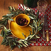 Wreath of olive leaves around bowl of olives