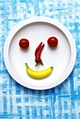Food collage: face made from banana, chili & tomatoes on plate
