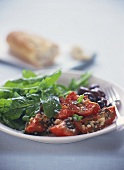 Toast with sheep's cheese, bottled tomatoes, olives, rocket