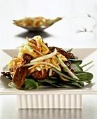 Pork with egg noodles on bed of lettuce