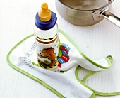 Säuglingsmilch in einer Babyflasche auf Lätzchen