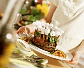 Woman putting a serving dish with rack of lamb on the table