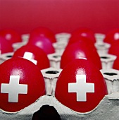 Dyed red eggs with Swiss cross in egg box