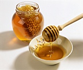 Honey dipper with fresh honey; jar with honeycomb