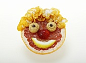 Face made from fruit, cornflakes and amarettini
