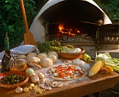 Unbaked pizza in front of pizza oven