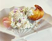 Herb quark with edible flowers and a piece of roll