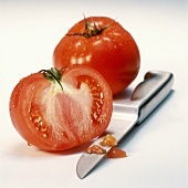 Half and whole beefsteak tomato with knife