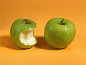 One whole Granny Smith apple and one with a bite taken
