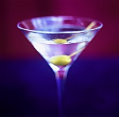 A glass of Martini with green olive