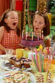 Two girls blowing out candles on birthday cake