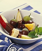 Assorted chocolate-coated fruits in a bowl