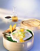 Steamed halibut fillet with vegetables in steaming basket
